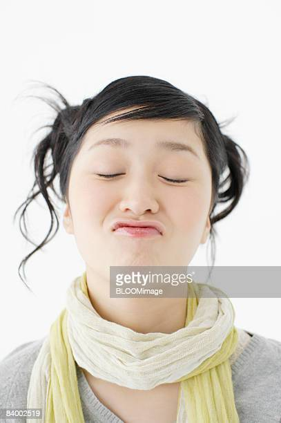 Portrait of teenage girl making funny face with eyes closed, close-up, studio shot