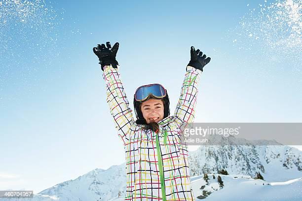 Portrait of teenage girl skier with arms raised, Les Arcs, Haute-Savoie, France