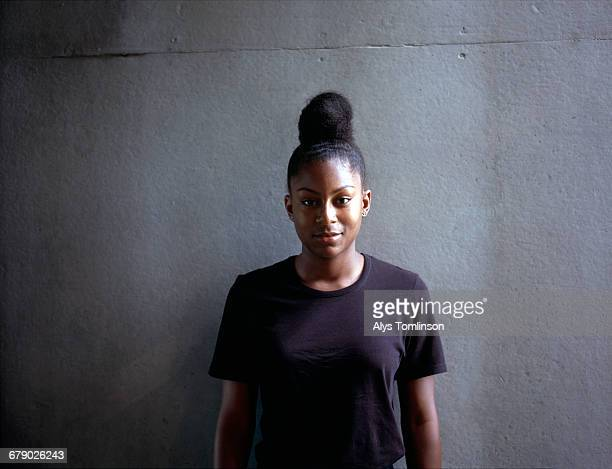 Portrait of teenage girl standing against wall