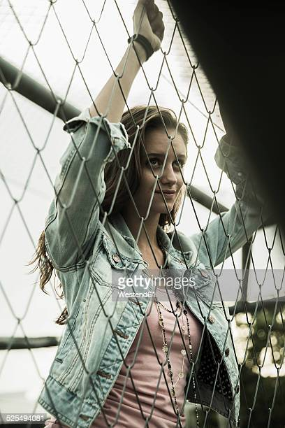 Portrait of teenage girl standing behind a wire fence
