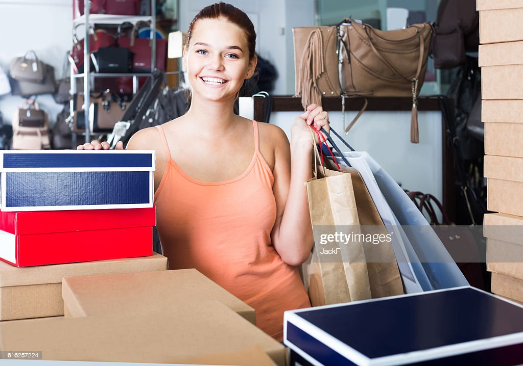 portrait of teenage girl standing with bags in store : Stock Photo