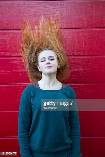 Portrait of teenage girl tossing her hair in front of red wooden wall