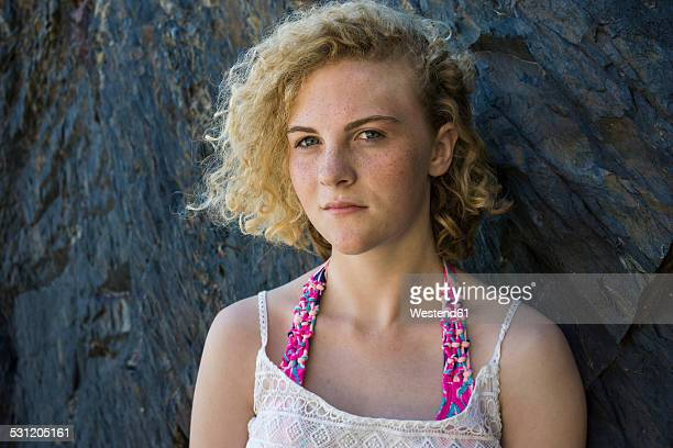 Portrait of teenage girl with freckles standing in front of a rock