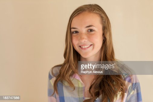 Portrait of teenage girl with long brown hair, smiling