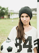 Portrait of teenage girl with soccer ball leaning at goalpost