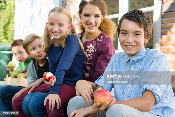 Portrait of teenagers and children sitting on patio eating apples