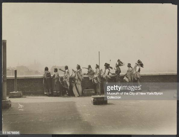 Portrait of ten Native Americans on the roof of the McAlpin Hotel pointing and looking toward the skyline New York New York 1913