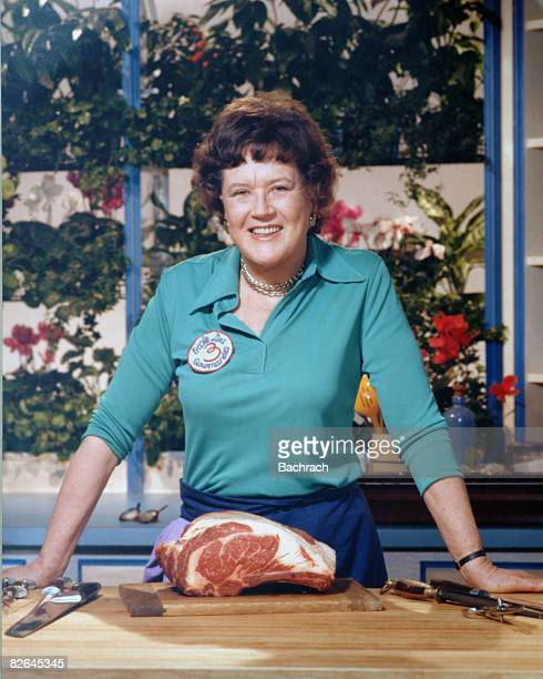 A portrait of the American chef Julia Child shows her standing with a cut of meat in her kitchen late 20th century
