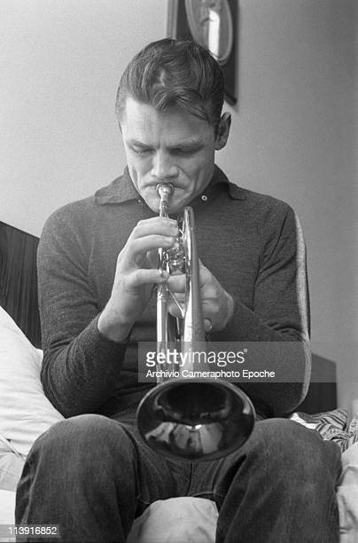 Portrait of the american jazz trumpeter Chesney Henry 'Chet' Baker sitting on a bed and playing trumpet Lucca 1961