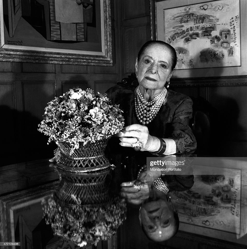 'Portrait of the American magnate <a gi-track='captionPersonalityLinkClicked' href=/galleries/search?phrase=Helena+Rubinstein&family=editorial&specificpeople=212912 ng-click='$event.stopPropagation()'>Helena Rubinstein</a> seated at a table next to a centerpiece with flowers in her beautiful house in the Fifth Avenue; at her backs a watercolor by Raoul Dufy and a cubist painting; Polish-born, she made an industrial empire out of the cosmetics company bearing her name. New York (USA), April 1964. (Photo by Mario De Biasi\Mondadori Portfolio via Getty Images)'