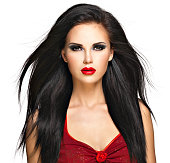 Portrait of  the beautiful woman with  black straight hairs and red lips, evening makeup. Pretty model posing at studio