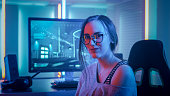Portrait of the Beautiful Young Pro Gamer Girl Sitting at Her Personal Computer and Looks into Camera. Attractive Geek Girl Player Wearing Glasses in the Room Lit by Neon Lights.