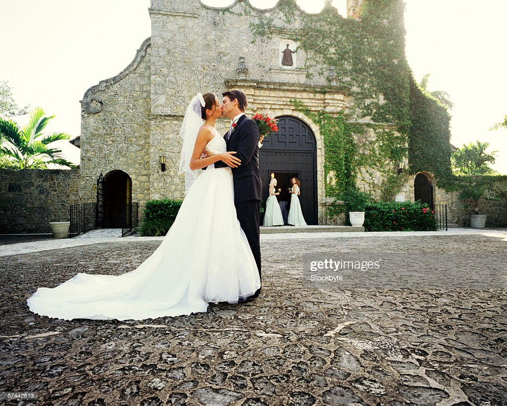 portrait of the bride and groom kissing outside a church : Stock Photo