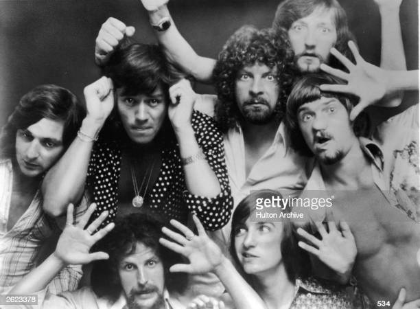 A portrait of the British rock band Electric Light Orchestra with their faces and hands pressed up against glass circa 1975