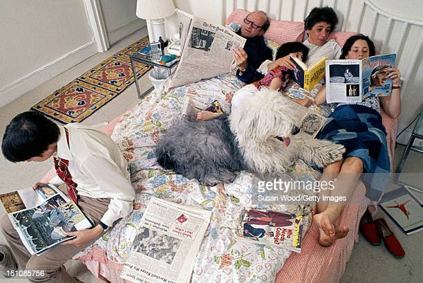 Portrait of the family of American editor of Newsweek magazine and former New York City deputy mayor Osborn Elliott as he reads in bed with his wife...