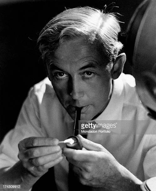 Portrait of the French movie director and screenwriter Robert Bresson photographed smoking a pipe former painter prisoner of German war camp during...