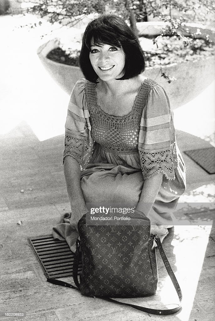 Portrait of the French singer and actress <a gi-track='captionPersonalityLinkClicked' href=/galleries/search?phrase=Juliette+Greco&family=editorial&specificpeople=210869 ng-click='$event.stopPropagation()'>Juliette Greco</a> smiling with a Louis Vuitton handbag. Rome, 1970s