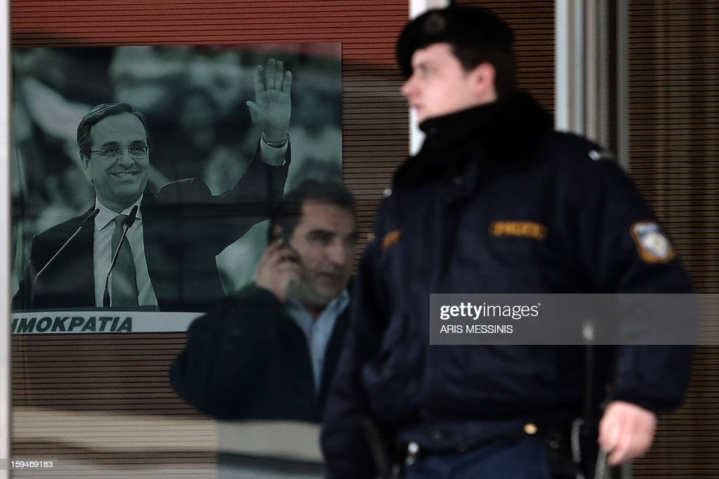 A portrait of the Greek Prime Minister and leader of the conservative party New Democracy Antonis Samaras is pictured as a riot police member stands outside the headquarters of New Democracy party on January 14, 2013. Shots were fired early on January 14, 2012 near the offices of main Greek ruling party New Democracy in Athens, police said, after a recent wave of arson attacks against political offices.