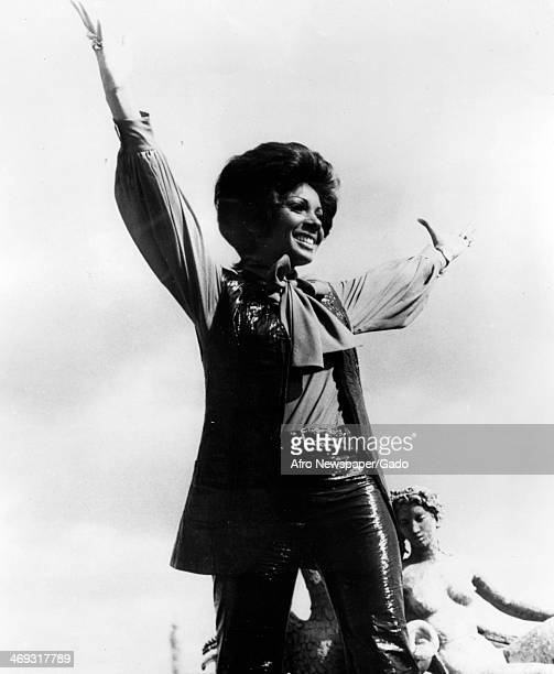 Portrait of the internationally renowned Welsh black singer Shirley Bassey raising her arms in acknowledgement of the crowd at an event 1966