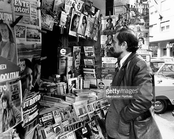 Portrait of the Italian actor Massimo Mollica stopping in front of a newspaper kiosk Rome 1973