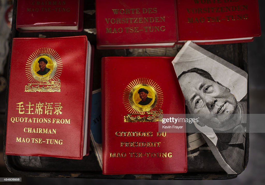 a portrait of the late chinese leader mao zedong is seen next to copies of his