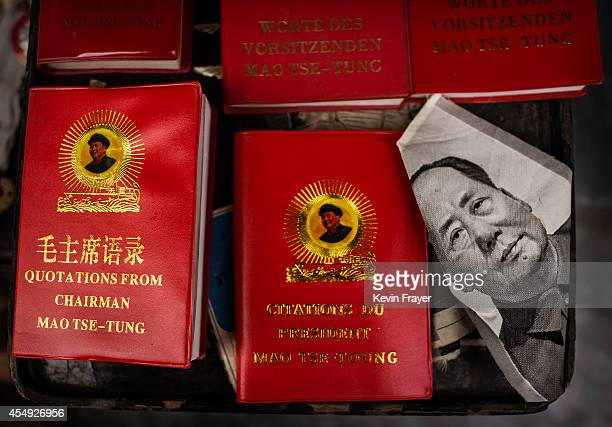 A portrait of the late Chinese leader Mao Zedong is seen next to copies of his famous 'Red Book' in various languages for sale at a vendor's stand at...
