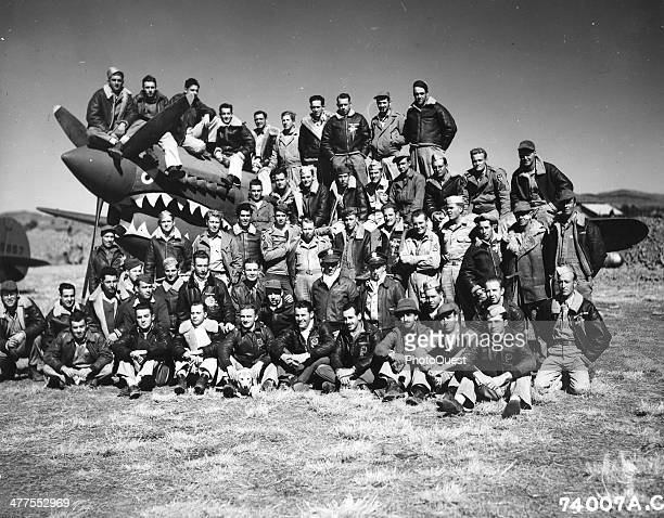 Portrait of the officers and enlisted men of the 74th Fighter Squadron 23rd Fighter Group as they pose on a Curtiss P40 Kunming China February 1 1943
