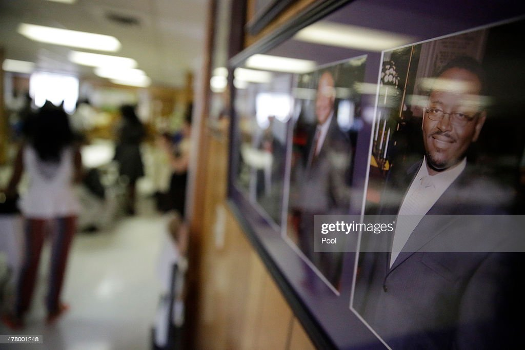 A portrait of the Rev. Clementa Pinckney, right hangs on a wall in the basement where a mass shooting claimed the lives of nine people at the historic Emanuel African Methodist Church June 21, 2015 in Charleston, South Carolina. Chruch elders decided to hold the regularly scheduled Sunday school and worship service as they continue to grieve the shooting death of nine of its members including its pastor earlier this week.