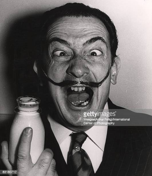 Portrait of the Spanish surrealist painter and sculptor Salvador Dali making an outrageous face with crossed eyes and open mouth while holding a...