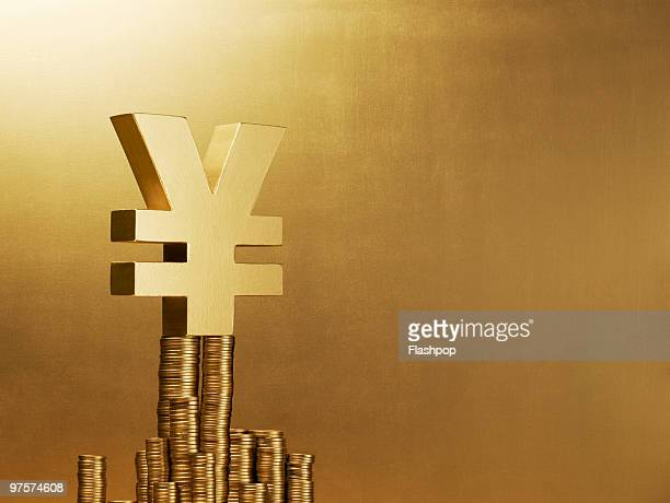 Portrait of the Yen sign balancing on gold coins