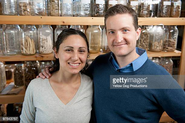 Portrait of therapists in front of herb jars