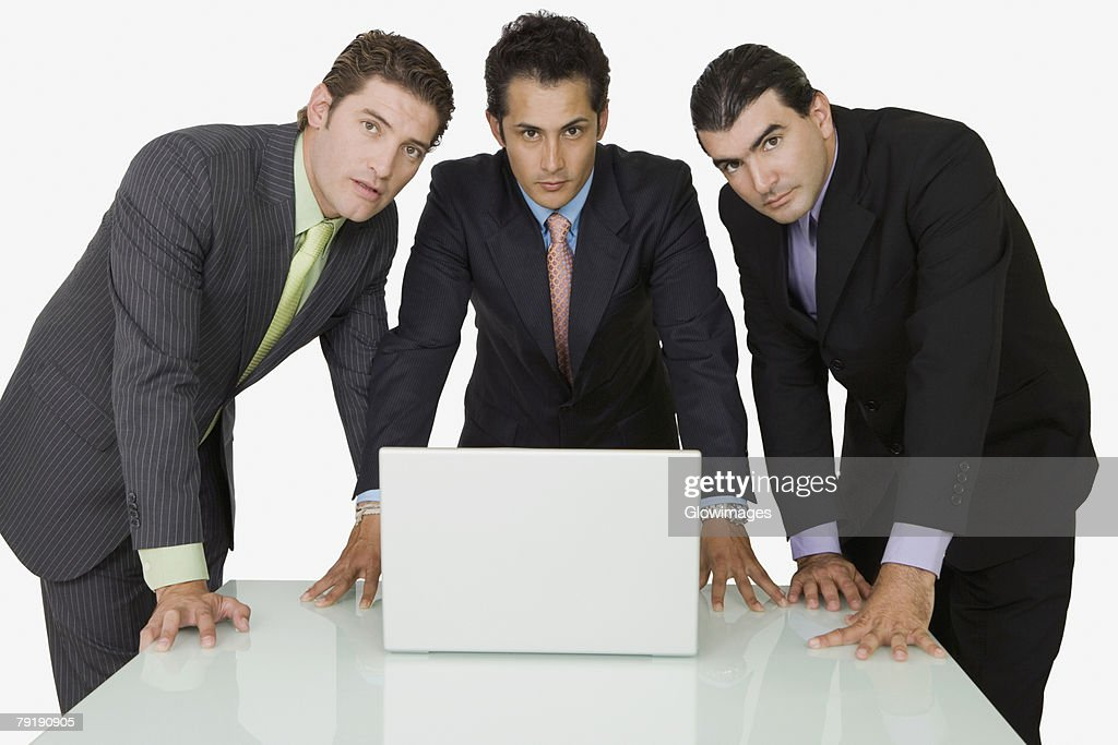 Portrait of three businessmen in front of a laptop : Stock Photo