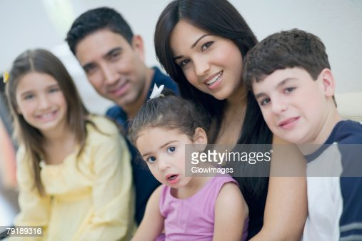 Portrait of three children sitting together with their parents : Stock Photo