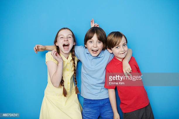 Portrait of three children with arms around each other against blue background