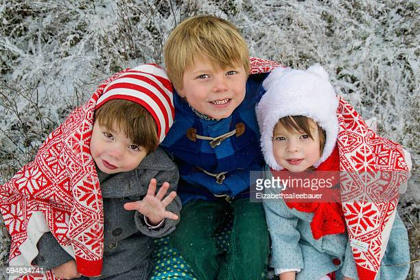 Portrait of three children wrapped in a blanket sitting outdoors