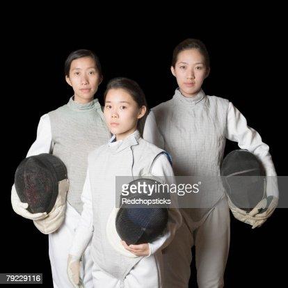 Portrait of three female fencers holding fencing masks