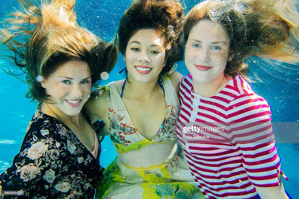 Portrait of three female swimmers, underwater, smiling