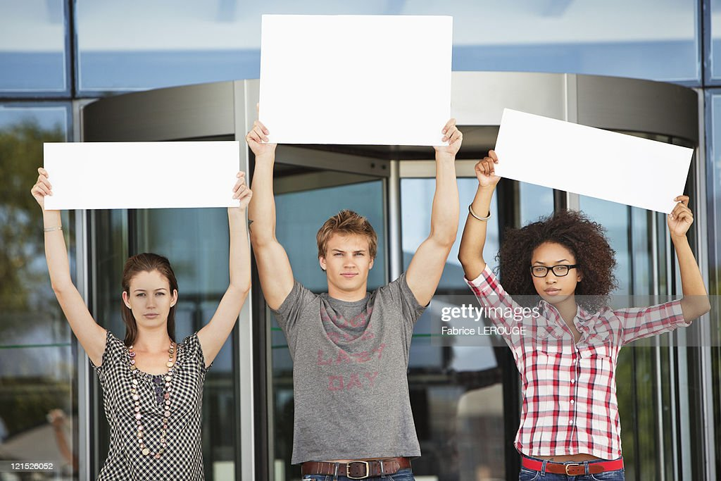 Portrait of three friends protesting with blank placards