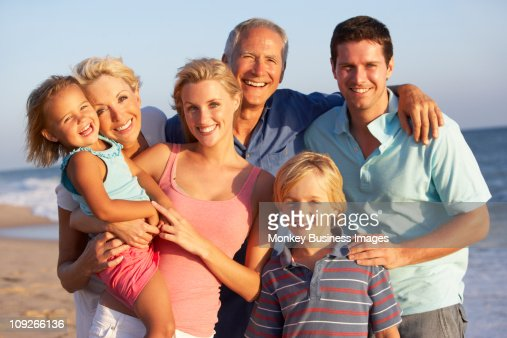 Portrait Of Three Generation Family On Beach Holiday : Stock Photo