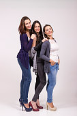 Portrait of three girls, in high heel shoes. Studio shot, white clean background