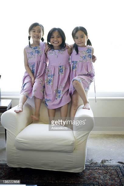 Portrait of three girls standing on an armchair