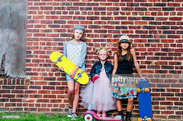 Portrait of three girls with skateboards and scooter in front of brick wall