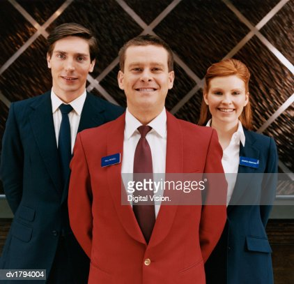 Portrait of Three Hotel Reception Staff Standing With Their Hands Behind Their Backs : Stock Photo