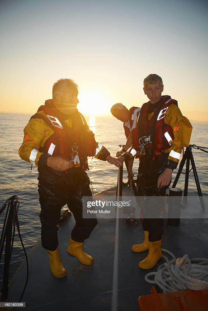 Portrait of three men holding lifeboat railing at sea