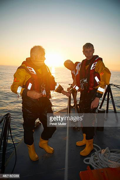 Portrait of three men holding lifeboat railing at sea