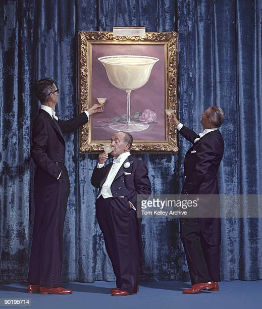 Portrait of three men of differing heights all dressed in tuxedos and all drinking margaritas underneath a large painting of a margarita mounted...