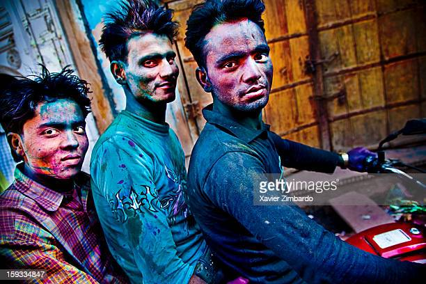 Portrait of three men on a motorbike covered with coloured powdered dye and coloured water that people throw on each other during Holi on March 11...