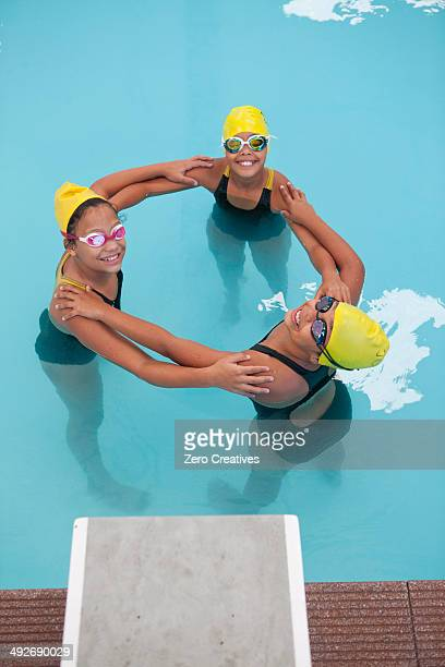 Portrait of three schoolgirl swimmers making circle