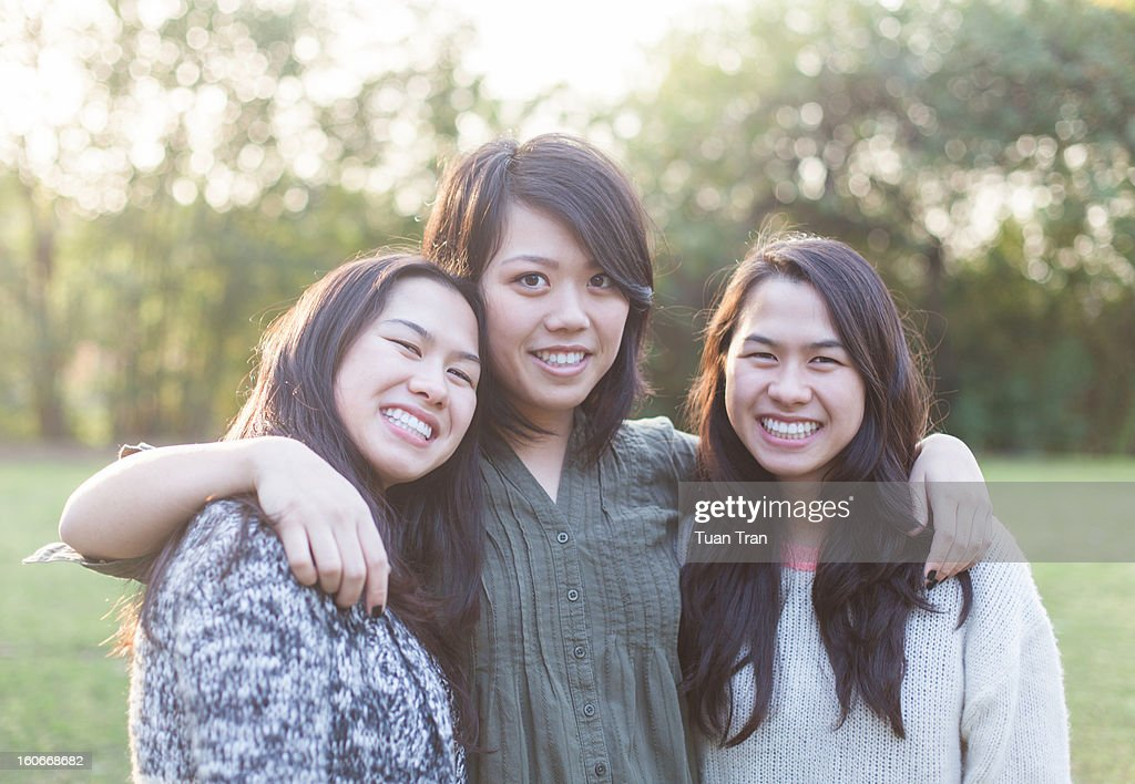 Portrait of three sisters smiling at the park : Stock Photo