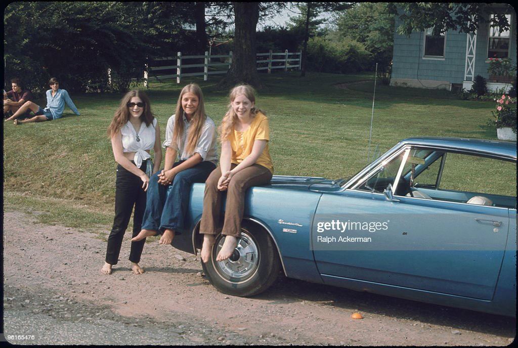 Portrait of three unidentiied and barefoot women two of whom are seated on the hood of a Plymouth Barracuda parked on the side of a gravel road near...